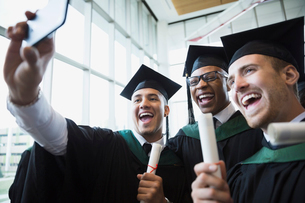 Enthusiastic college graduates cap and gown taking selfieの写真素材 [FYI02276310]