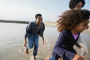 Playful family running on beachの写真素材 [FYI02276321]