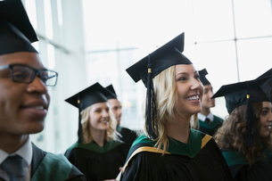 Enthusiastic college graduates cap and gown looking awayの写真素材 [FYI02276338]
