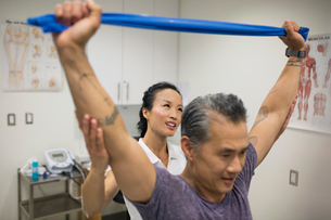 Physical therapist guiding patient pulling resistance bandの写真素材 [FYI02276351]
