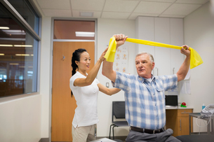 Physical therapist guiding patient with resistance bandの写真素材 [FYI02276427]