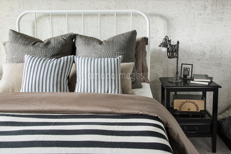 Striped and patterned pillows and blanket on bedの写真素材 [FYI02276458]