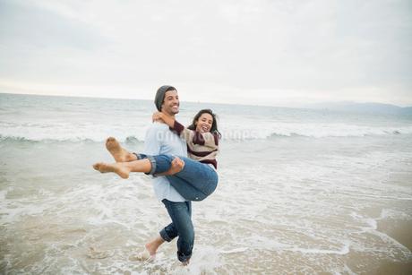 Playful boyfriend carrying girlfriend in ocean surfの写真素材 [FYI02276539]