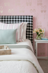 Pastel pillows on bed with gingham headboardの写真素材 [FYI02276544]