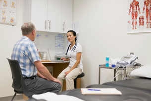 Physical therapist and patient talking in examination roomの写真素材 [FYI02276554]