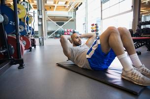 Man doing sit-ups on mat at gymの写真素材 [FYI02276587]