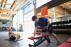 Man doing dumbbell rows on bench at gymの写真素材 [FYI02276601]