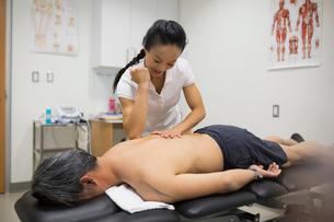 Physical therapist using elbow to massage patient backの写真素材 [FYI02276606]