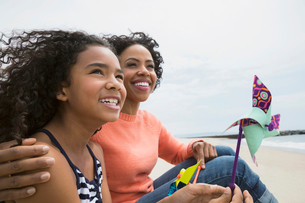 Smiling mother and daughter with pinwheel on beachの写真素材 [FYI02276620]