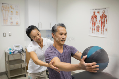 Physical therapist guiding patient holding medicine ballの写真素材 [FYI02276628]