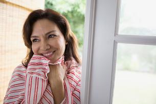 Smiling brunette woman wrapped in towel in doorwayの写真素材 [FYI02276632]