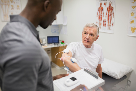 Physical therapist talking to patient with electrodes armの写真素材 [FYI02276714]