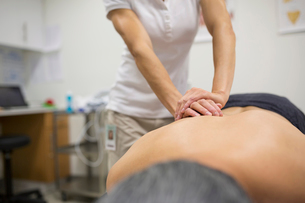 Physical therapist massaging patient backの写真素材 [FYI02276730]