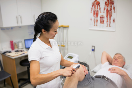 Physical therapist using ultrasound probe on patient kneeの写真素材 [FYI02276731]