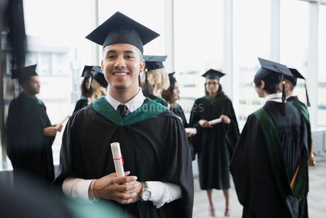 Portrait confident college graduate cap and gown diplomaの写真素材 [FYI02276756]