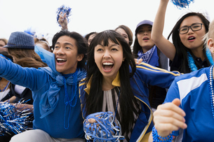Enthusiastic fans in blue cheering bleachers sports eventの写真素材 [FYI02276762]