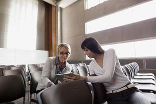 Women using digital tablet in auditoriumの写真素材 [FYI02276786]