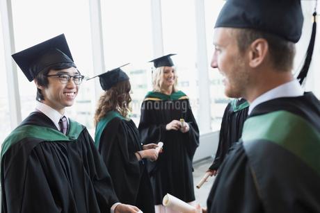 College graduates in cap and gown talkingの写真素材 [FYI02276788]