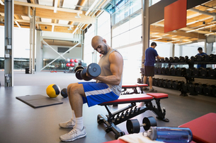 Man doing dumbbell biceps curls bench at gymの写真素材 [FYI02276790]