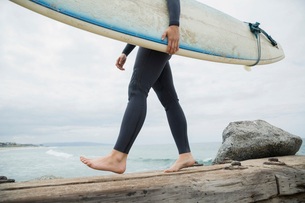 Barefoot female surfer with surfboard walking beach jettyの写真素材 [FYI02276817]