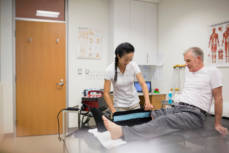 Physical therapist using compression knee wrap on patientの写真素材 [FYI02276822]