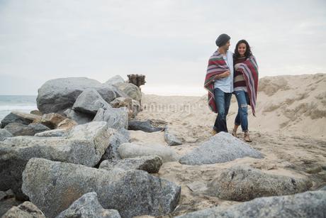 Couple wrapped in blanket walking beach along rocksの写真素材 [FYI02276857]