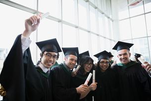 Portrait enthusiastic college graduates in cap and gownの写真素材 [FYI02276901]