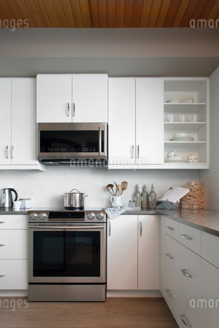 Modern white kitchen with stainless steel appliancesの写真素材 [FYI02276945]