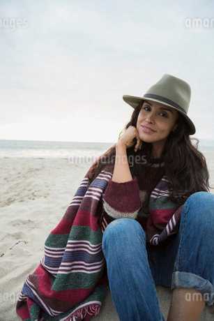 Portrait confident woman hat wrapped in blanket beachの写真素材 [FYI02276983]