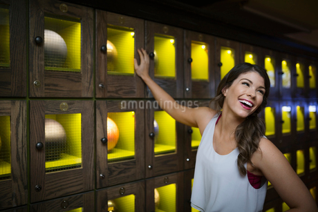 Laughing young woman leaning on bowling ball lockersの写真素材 [FYI02277006]