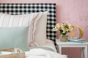 Pastel pillows on bed with gingham headboardの写真素材 [FYI02277010]