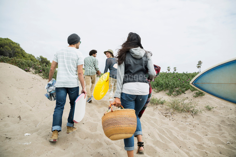 Friends carrying belongings on beach pathの写真素材 [FYI02277029]