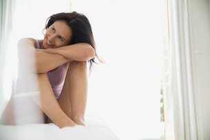 Smiling brunette woman hugging knees on bedの写真素材 [FYI02277085]