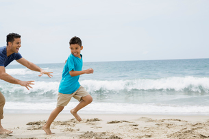 Father running and chasing son on beachの写真素材 [FYI02277154]