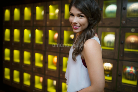 Portrait smiling young woman near bowling ball lockersの写真素材 [FYI02277162]