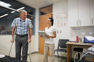 Physical therapist and patient on crutches examination roomの写真素材 [FYI02277231]