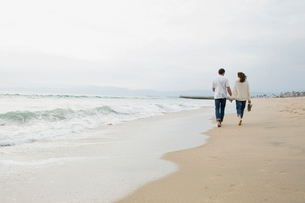 Couple holding hands and walking on beachの写真素材 [FYI02277246]