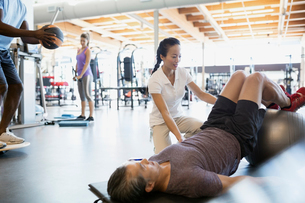 Physical therapist guiding patient fitness ball bridge poseの写真素材 [FYI02277253]