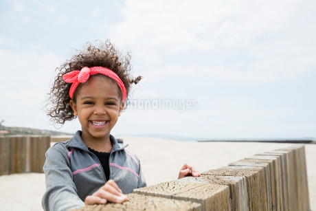 Portrait smiling girl curly hair at beach wallの写真素材 [FYI02277265]