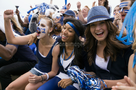 Enthusiastic fans in blue cheering bleachers sports eventの写真素材 [FYI02277297]