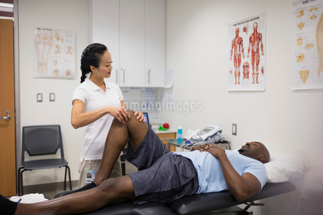 Physical therapist massaging patient knee in examination roomの写真素材 [FYI02277359]