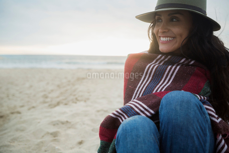 Smiling brunette woman hat wrapped in blanket beachの写真素材 [FYI02277367]