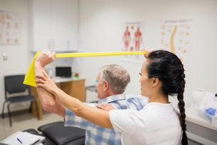 Physical therapist guiding patient with resistance bandの写真素材 [FYI02277379]
