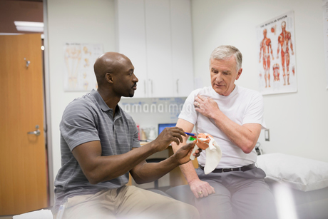 Physical therapist explaining shoulder pain patient with modelの写真素材 [FYI02277392]