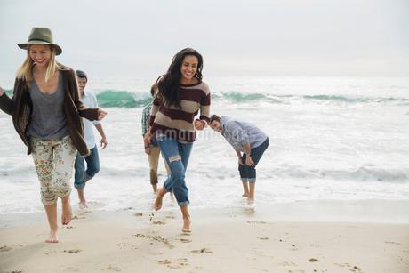 Friends running from ocean surf onto beachの写真素材 [FYI02277412]