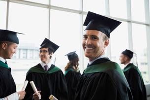 Portrait confident college graduate in cap and gownの写真素材 [FYI02277422]