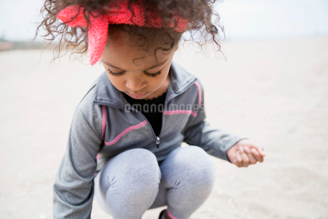 Girl with curly hair crouching on beachの写真素材 [FYI02277446]