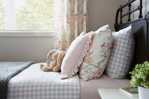 Pastel and gingham pillows on bed stuffed animalsの写真素材 [FYI02277470]