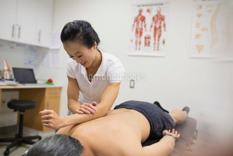 Physical therapist using forearm to massage patient backの写真素材 [FYI02277504]