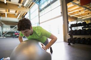Man doing fitness ball push-ups at gymの写真素材 [FYI02277507]